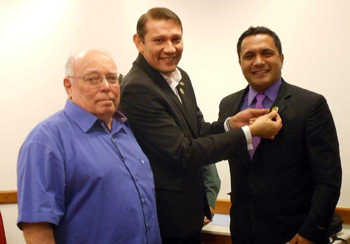 Eduardo recebendo o pin das mãos do último homologado, junto com o diretor Ricardo Farias